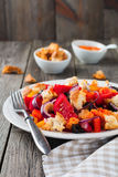 Sallad med peppar, tomater, lökar, oliv och krutonger med gammal träbakgrund för sousomna Arkivbilder