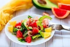Sallad med räkor, avokadot och grapefrukten på en ljus bakgrund Royaltyfria Bilder