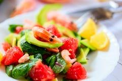 Sallad med räkor, avokadot och grapefrukten på en ljus bakgrund Arkivfoto