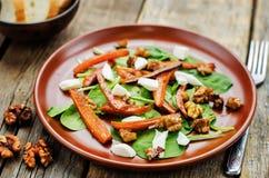 Sallad med spenat, mozzarellaen, valnötter och caramelized morötter Arkivbild