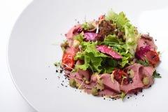 Sallad med steknötkött, tonfisk och ansjovissås isolerat Royaltyfri Foto