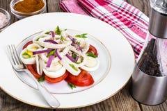 Sallad med tioarmade bläckfisken, ägget och tomaten på den vita plattan på bakgrund av Royaltyfri Foto