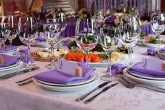Sallader och tomma vinexponeringsglas ställde in i restaurangen Royaltyfri Bild