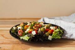 Salladgrek, ovoshny sallad, tomater, oliv, ost, sund mat, en banta med sallad, mycket aptitretande sallad på en trätabell arkivfoto