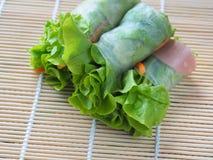 Salladrulle inkluderar nya grönsaker, morötter, krabbapinnar på bambuskivor som vävas i ren sund och viktcontr för mat för begrep arkivbild