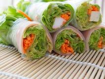 Salladrulle inkluderar nya grönsaker, morötter, krabbapinnar på bambuskivor som vävas i ren sund och viktcontr för mat för begrep arkivbilder