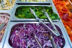 Salladst?ng i matsalen högg av purpurfärgade lökar grön sallad, röd peppar, bacon royaltyfri bild