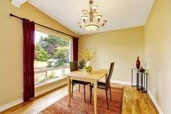 Salle à manger avec l'ensemble de table, le plancher en bois dur et les rideaux rouges Images stock