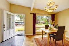Salle à manger avec l'ensemble de table, le plancher en bois dur et les rideaux rouges Photo stock