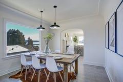 Salle à manger avec les murs blancs et la table en bois photographie stock