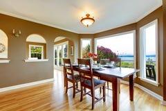 Salle à manger avec les murs bruns et la table en bois. Photographie stock libre de droits