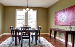Salle à manger avec les murs verts et la peinture rouge. image stock