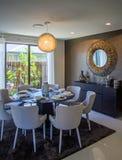 Salle à manger confortable avec le miroir de huit chaises sur le regard de mur à la barrière en bambou photos stock