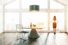 Salle à manger de grenier, fenêtre et table ronde, femme photographie stock