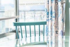Salle à manger lumineuse contre une fenêtre du sol au plafond, avec une chaise traditionnelle bleue et une table en verre Décor à photo libre de droits