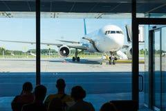 Salle d'attente à l'aéroport, foyer sur un avion Photo stock