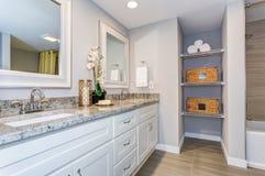 Salle de bains élégante avec le long coffret blanc de vanité images stock