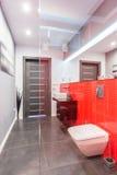 Salle de bains avec le mur carrelé rouge photo stock