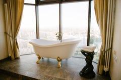 Salle de bains blanche libre avec des vues de ville dans la maison photos stock