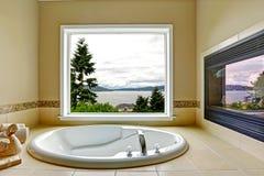 Salle de bains de luxe avec la vue de cheminée et de baie Photographie stock libre de droits