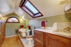 Salle de bains de vintage avec le plancher en bois dur et le plafond voûté photographie stock