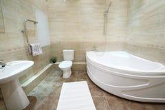 Salle de bains légère et propre avec la toilette avec des tuiles sur le plancher Images libres de droits