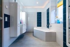 Salle de bains moderne - tuiles blanches et bleues brillantes - baignoire, évier et chauffage par le sol photo stock