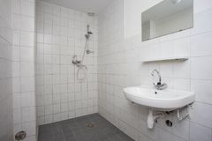 Salle de bains propre simple et vieille avec l'évier carrelé blanc de plancher et douche images libres de droits