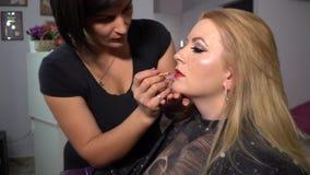 Salle de beauté Jeune beau modèle de fille se reposant dans la chaise Le maquilleur fait des filles de maquillage Blonde dans une banque de vidéos