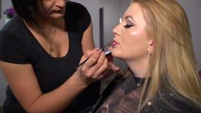 Salle de beaut? Jeune beau mod?le de fille se reposant dans la chaise Le maquilleur fait des filles de maquillage Blonde dans une clips vidéos