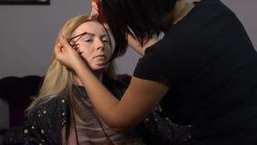 Salle de beaut? Le jeune beau mod?le de fille se repose dans la chaise Le maquilleur fait le maquillage de fille Maquilleur clips vidéos