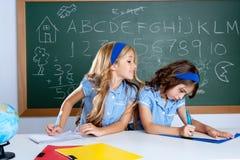 Salle de classe avec deux étudiants de gosses trichant sur l'essai Photographie stock libre de droits