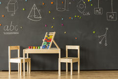 Salle de classe avec le tableau noir et peu de meubles Images stock