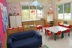 Salle de classe dans un jardin d'enfants avec des tables et des chaises et sofa bleu Photo libre de droits