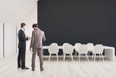 Salle de conférence noire dans le grenier, hommes Photo stock