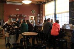 Salle de dégustation avec plusieurs personnes recueillies pour rattraper la vie, distillerie noire de bouton, Rochester, New York Photos libres de droits