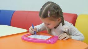 Salle de jeux du ` s d'enfants La petite fille mignonne peint sur un stylo spécial de tableau noir magnétique banque de vidéos