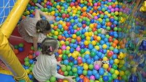 Salle de jeux du ` s d'enfants Les enfants jouent dans un bassin sec rempli de boules colorées en plastique banque de vidéos