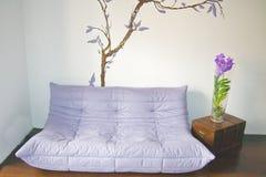 Salle de séjour avec le sofa pourpré et l'orchidée bleue Photos stock