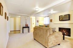 Salle de séjour lumineuse de sous-sol avec la cheminée. Photographie stock