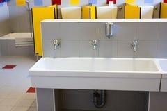 Salles de bains d'une école pour des enfants avec de bas éviers en céramique Image stock