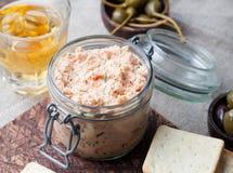Salmão fumado e queijo de barrar macio, musse, pasta em um frasco com biscoitos e alcaparras em um fundo de madeira Fotos de Stock Royalty Free