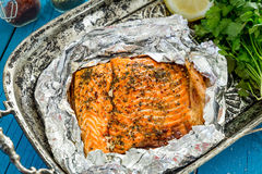 Salmões cozidos saborosos dos peixes na folha na tabela azul, vista superior imagens de stock royalty free