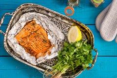 Salmões cozidos saborosos dos peixes na folha na tabela azul, vista superior imagens de stock