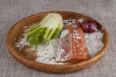 Salmões crus frescos em uma bandeja de madeira com salsa, sal e aipo Fotografia de Stock Royalty Free
