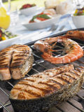 Salmões e camarões que cozinham em uma grade Fotos de Stock