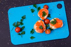 Salmões em uma cereja fresca do bruschetta e dos tomates entre três canapes Fotos de Stock Royalty Free