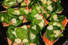 Salmões frescos com os legumes frescos na placa de corte preta foto de stock