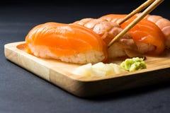 Salmões japoneses do sushi no preto Fotos de Stock Royalty Free