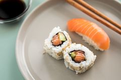 Salmões japoneses Nigiri e interior - para fora sushi de Califórnia com abacate, molho de soja e os hashis de madeira na placa da imagens de stock royalty free